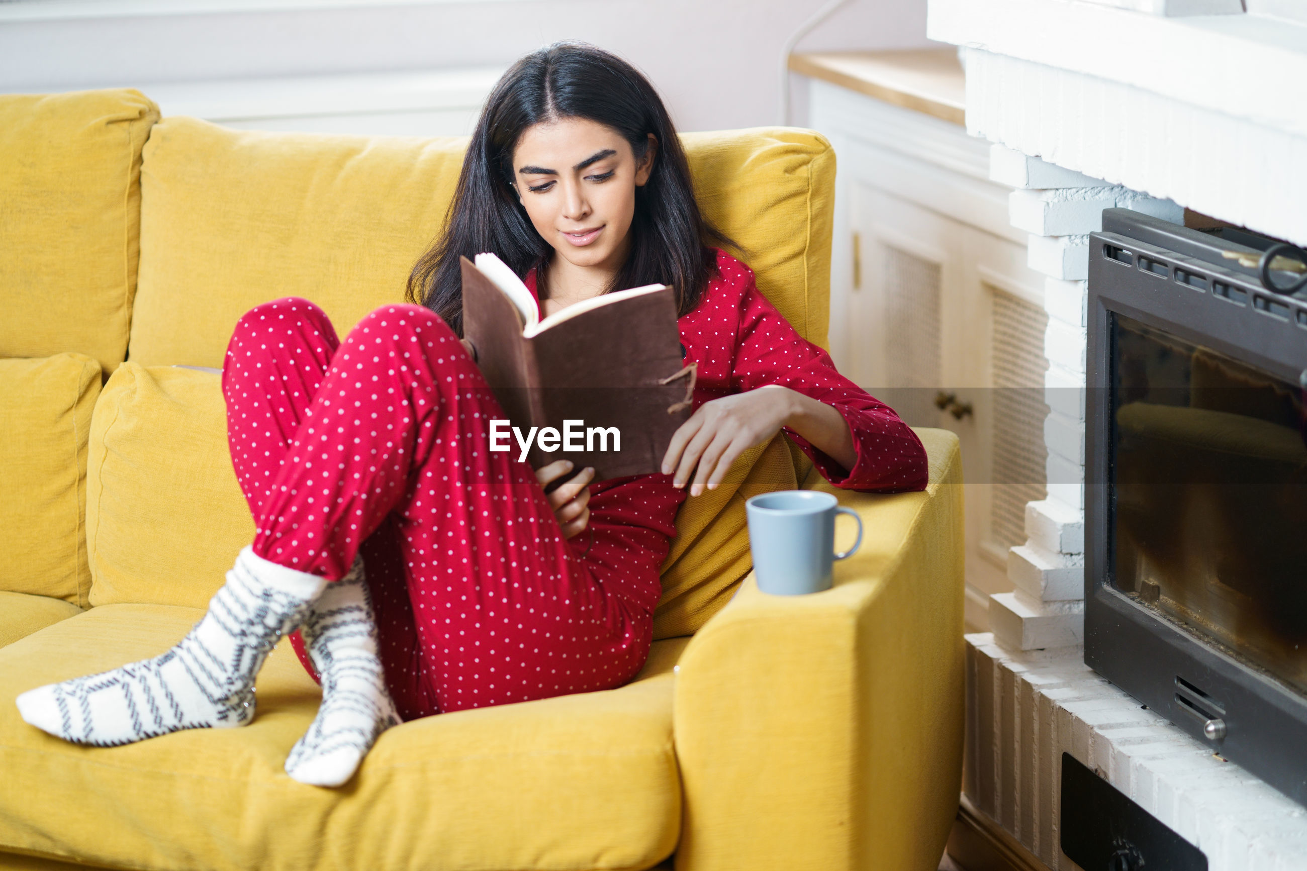 Young woman sitting on sofa reading book at home
