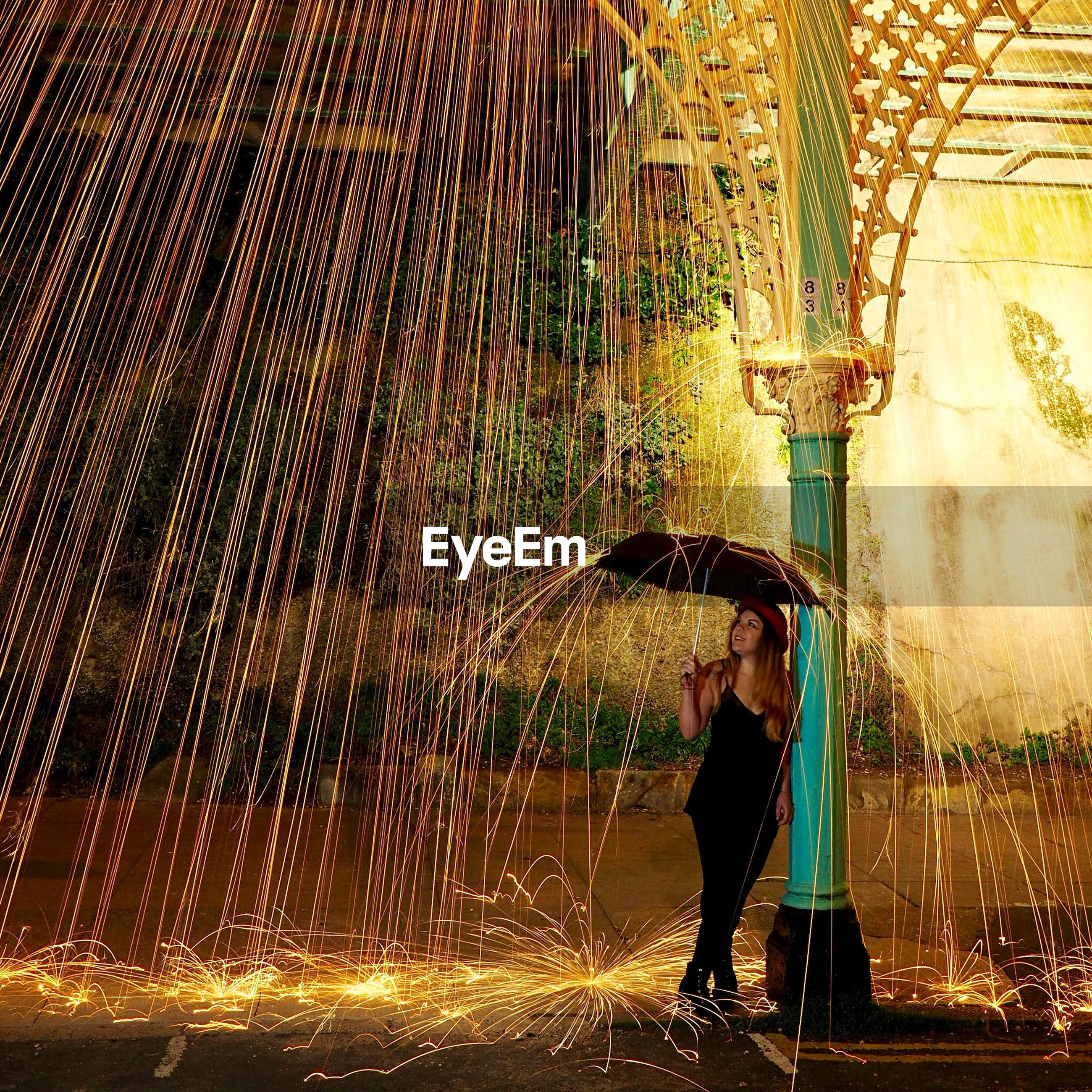 Woman with umbrella standing by wire wool