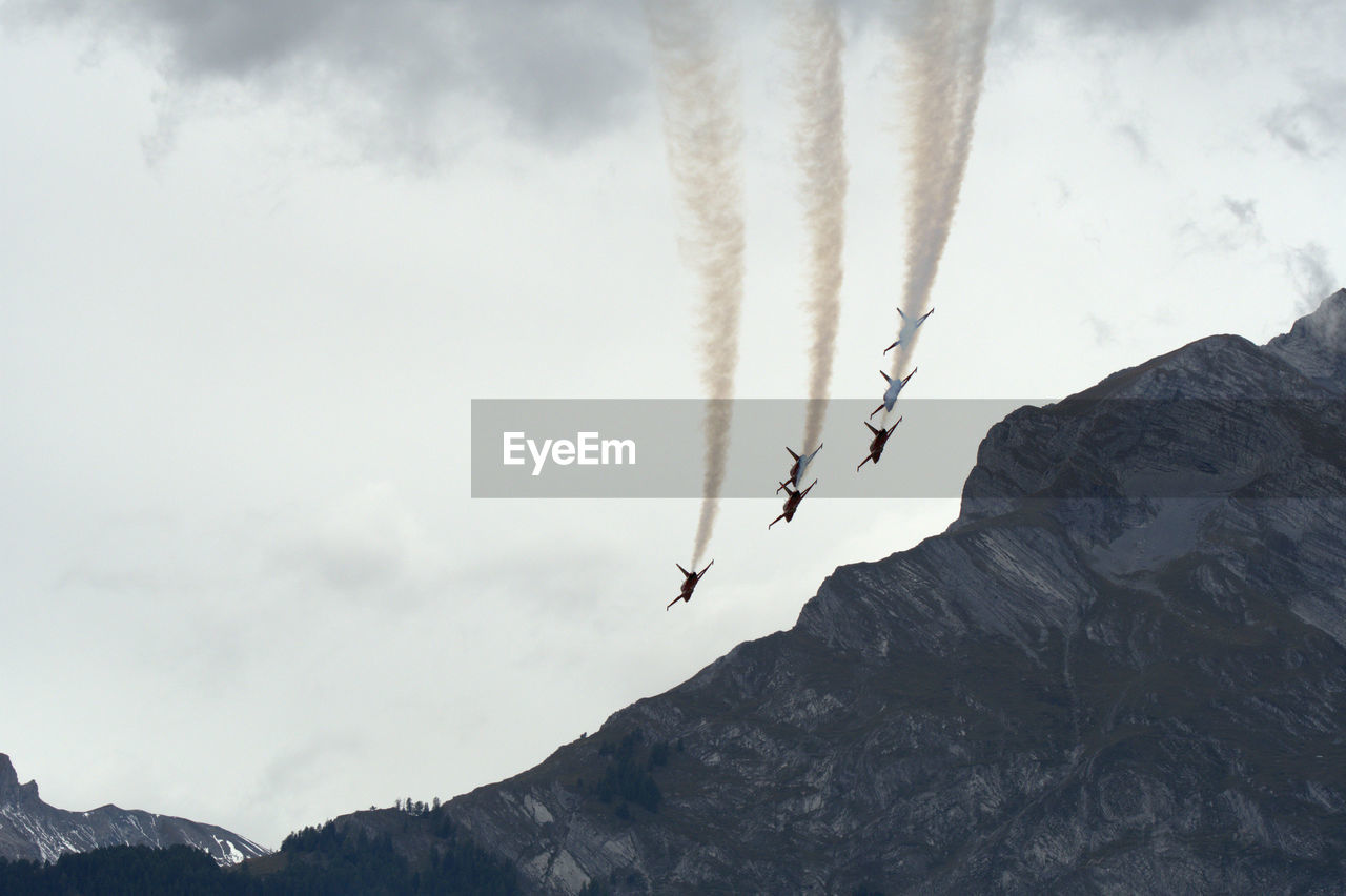 Low angle view of jet planes emitting vapor trail over mountains in sky