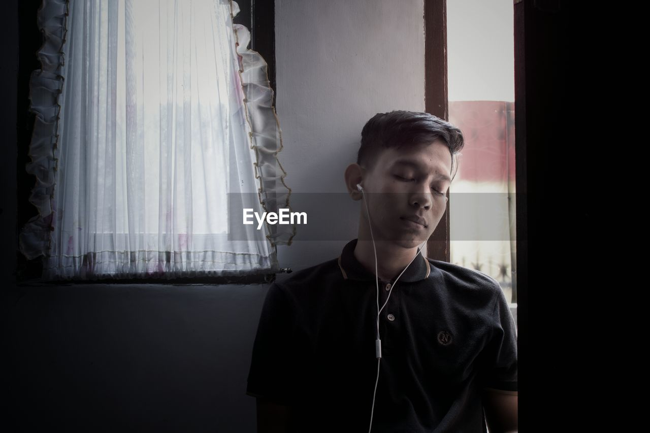 Man with closed eyes listening music while standing against wall at home