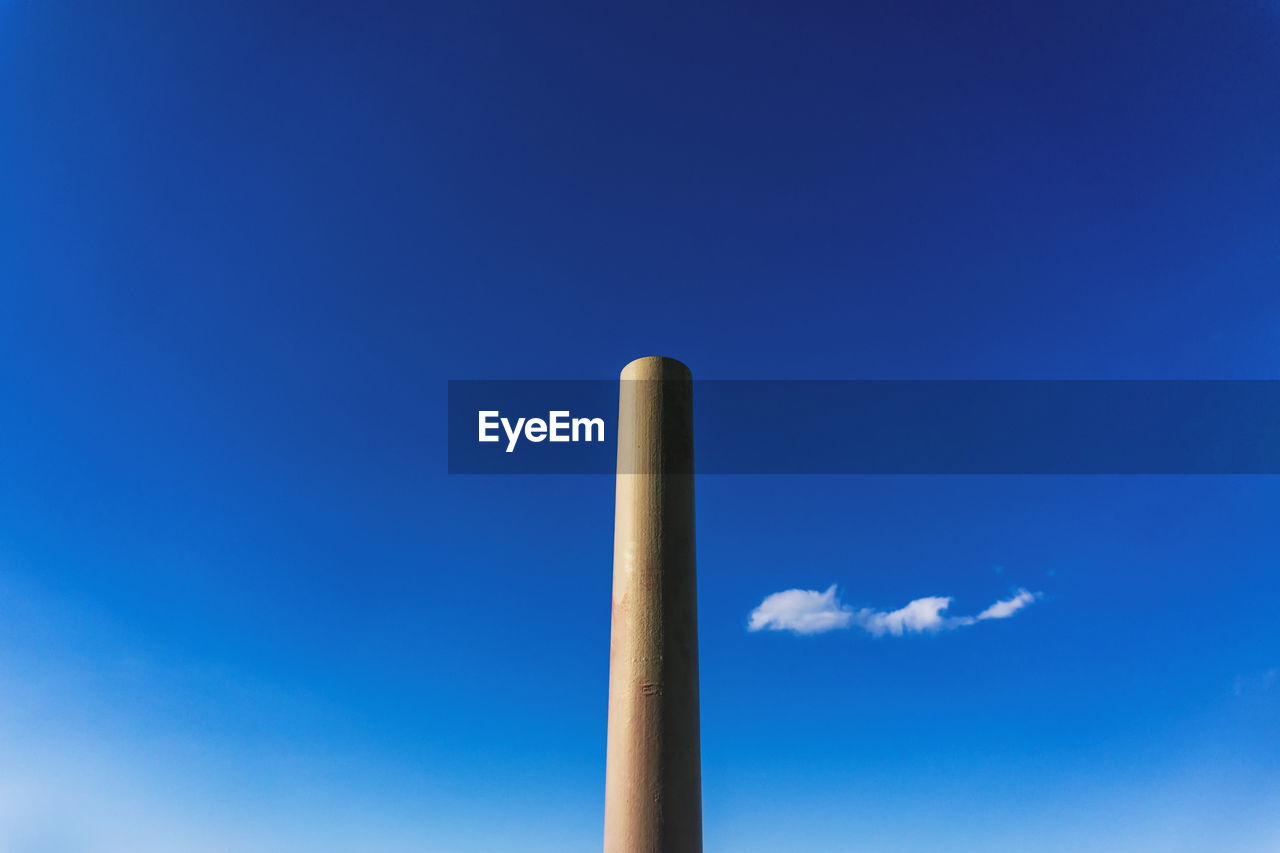 blue, sky, low angle view, no people, nature, copy space, smoke stack, day, factory, cloud - sky, industry, chimney, smoke - physical structure, outdoors, environmental issues, tall - high, emitting, sunlight, building exterior, pollution, air pollution