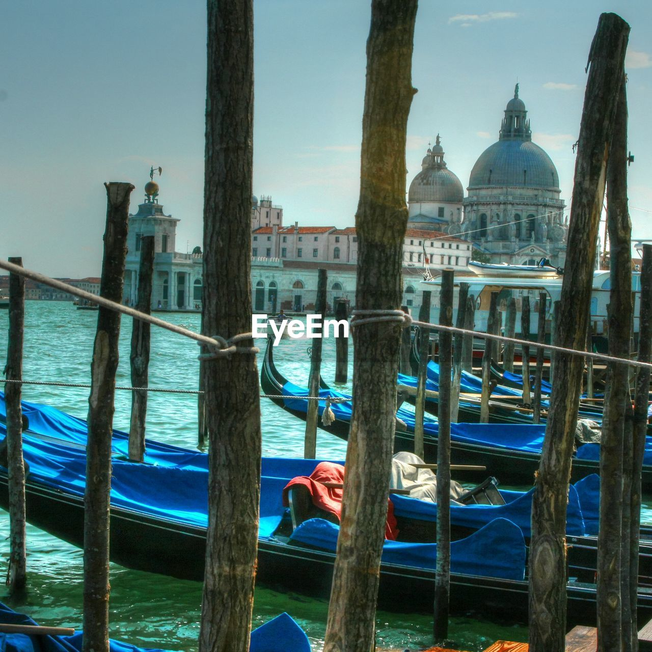 architecture, nautical vessel, travel destinations, gondola - traditional boat, place of worship, transportation, built structure, religion, canal, moored, water, building exterior, mode of transport, dome, gondola, spirituality, blue, outdoors, travel, day, wooden post, no people, sky, nature