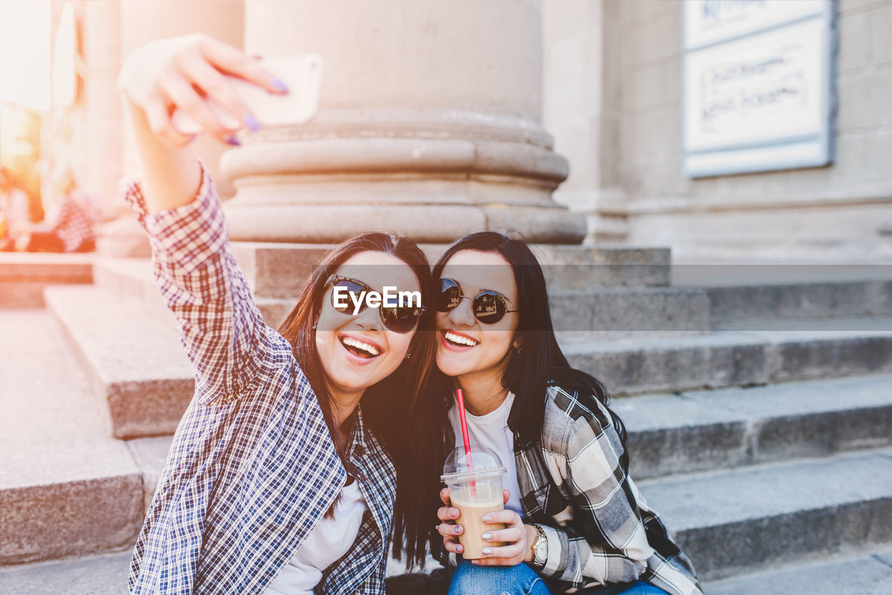 Smiling friends taking selfie with mobile phone in city