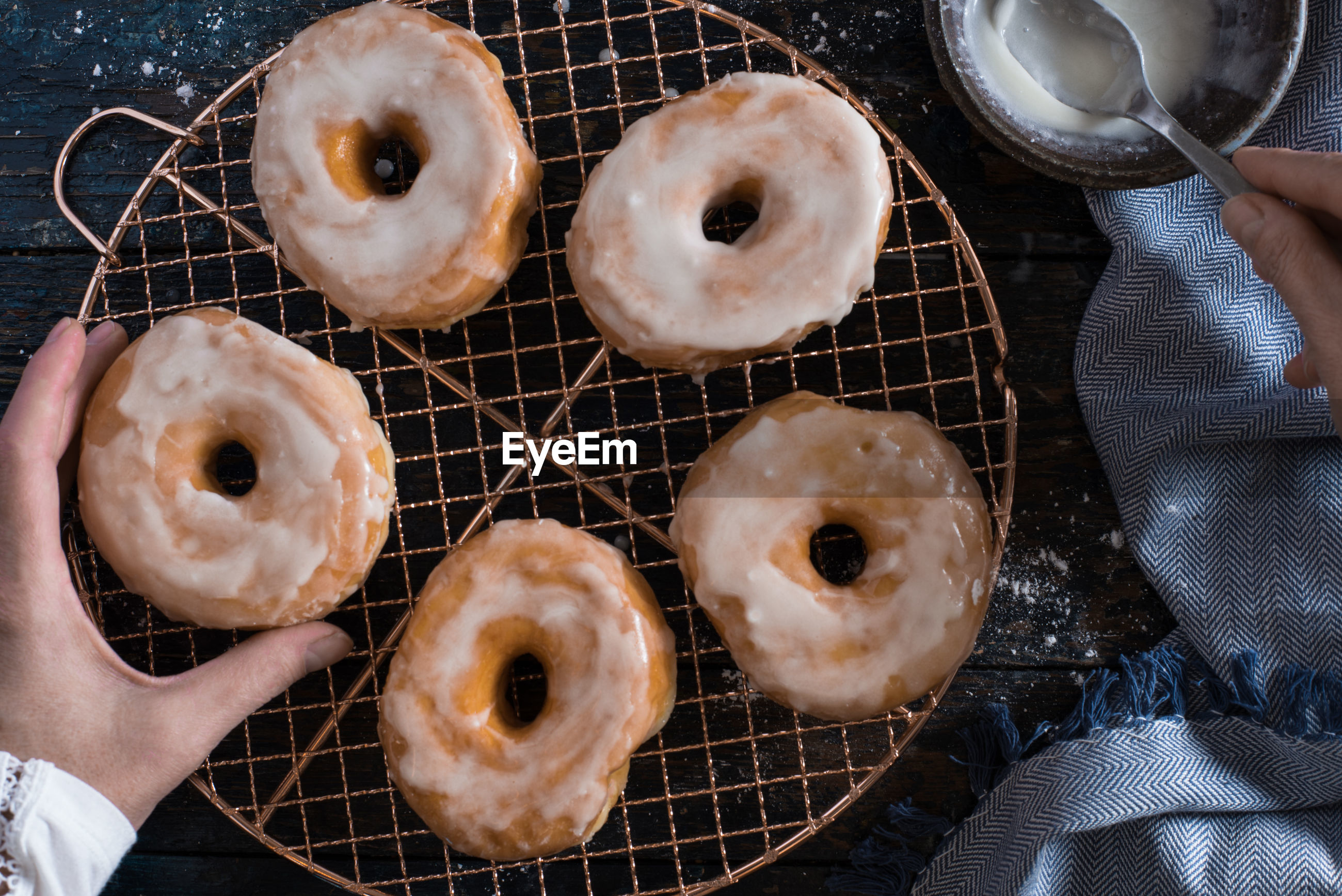 Cropped hands preparing donut on table
