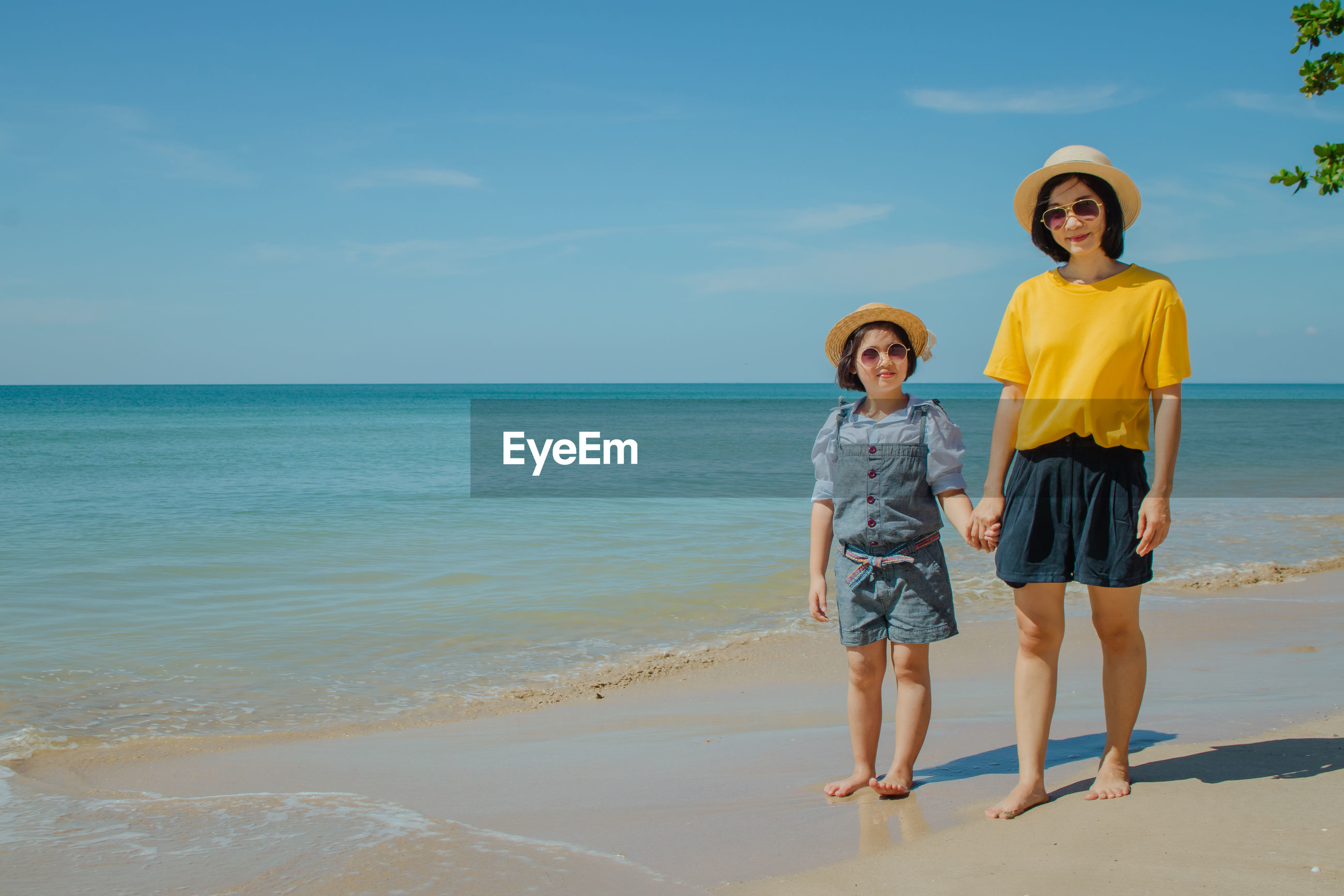 Mother and daughter at beach on sunny day