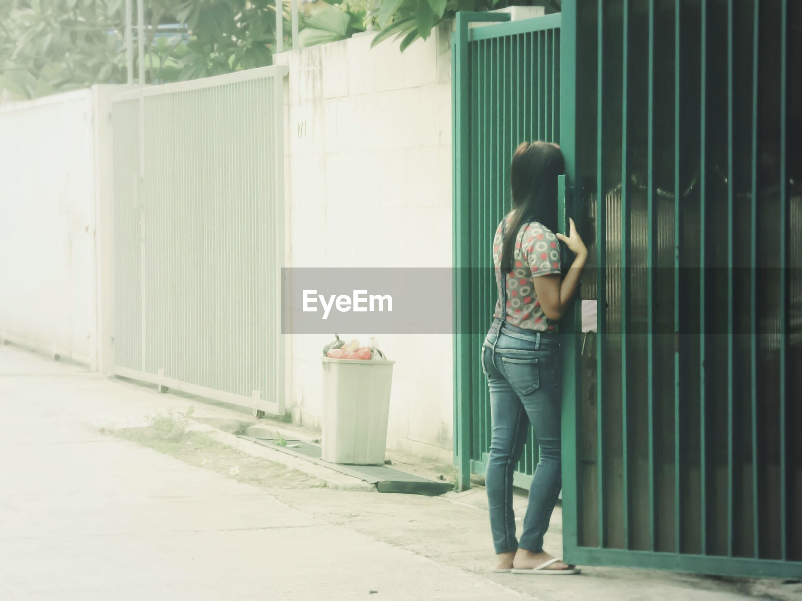 Rear view of woman standing by gate