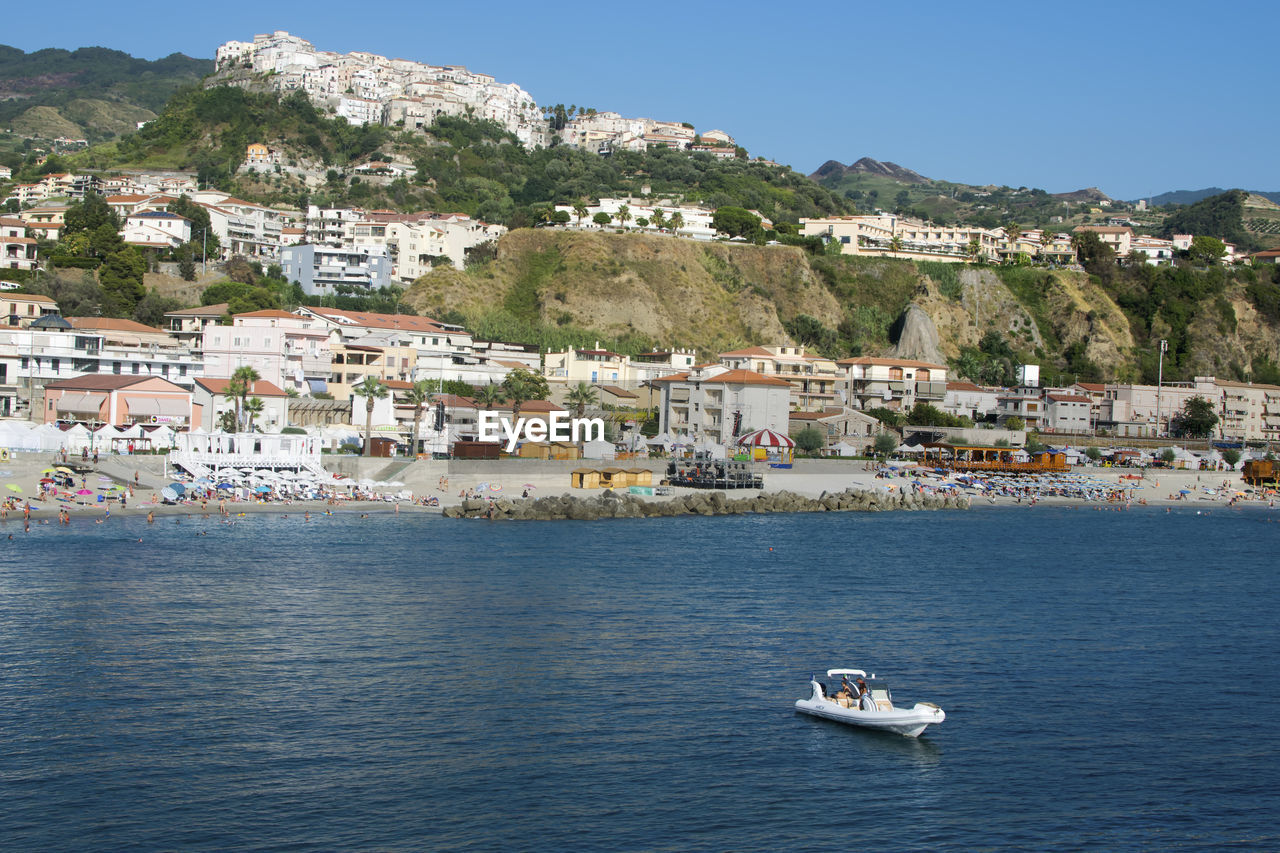 Scenic View Of Sea And Townscape Against Sky