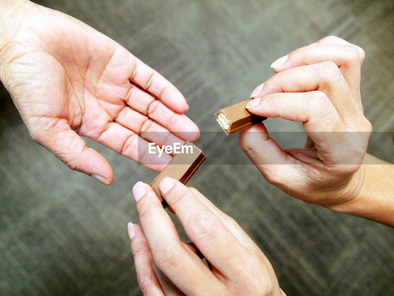 HIGH ANGLE VIEW OF PEOPLE HOLDING HANDS ON CROPPED HAND
