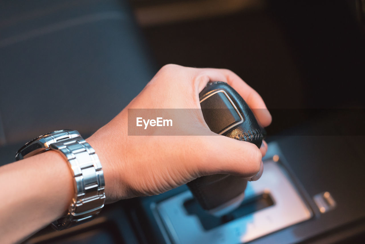 Cropped Hand Of Man Holding Gearshift In Car