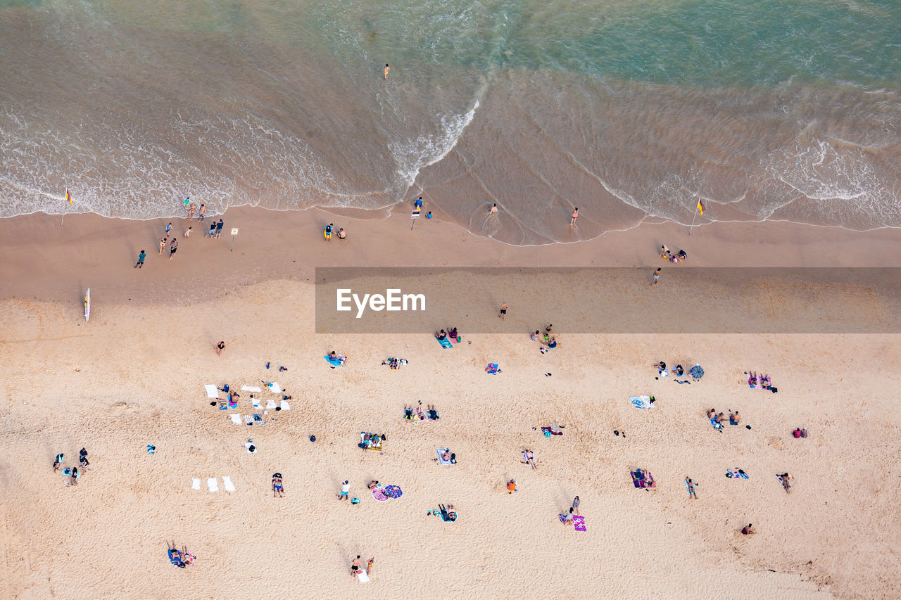 land, sand, crowd, group of people, large group of people, real people, beach, nature, day, vacations, water, leisure activity, trip, holiday, beauty in nature, lifestyles, high angle view, scenics - nature, outdoors