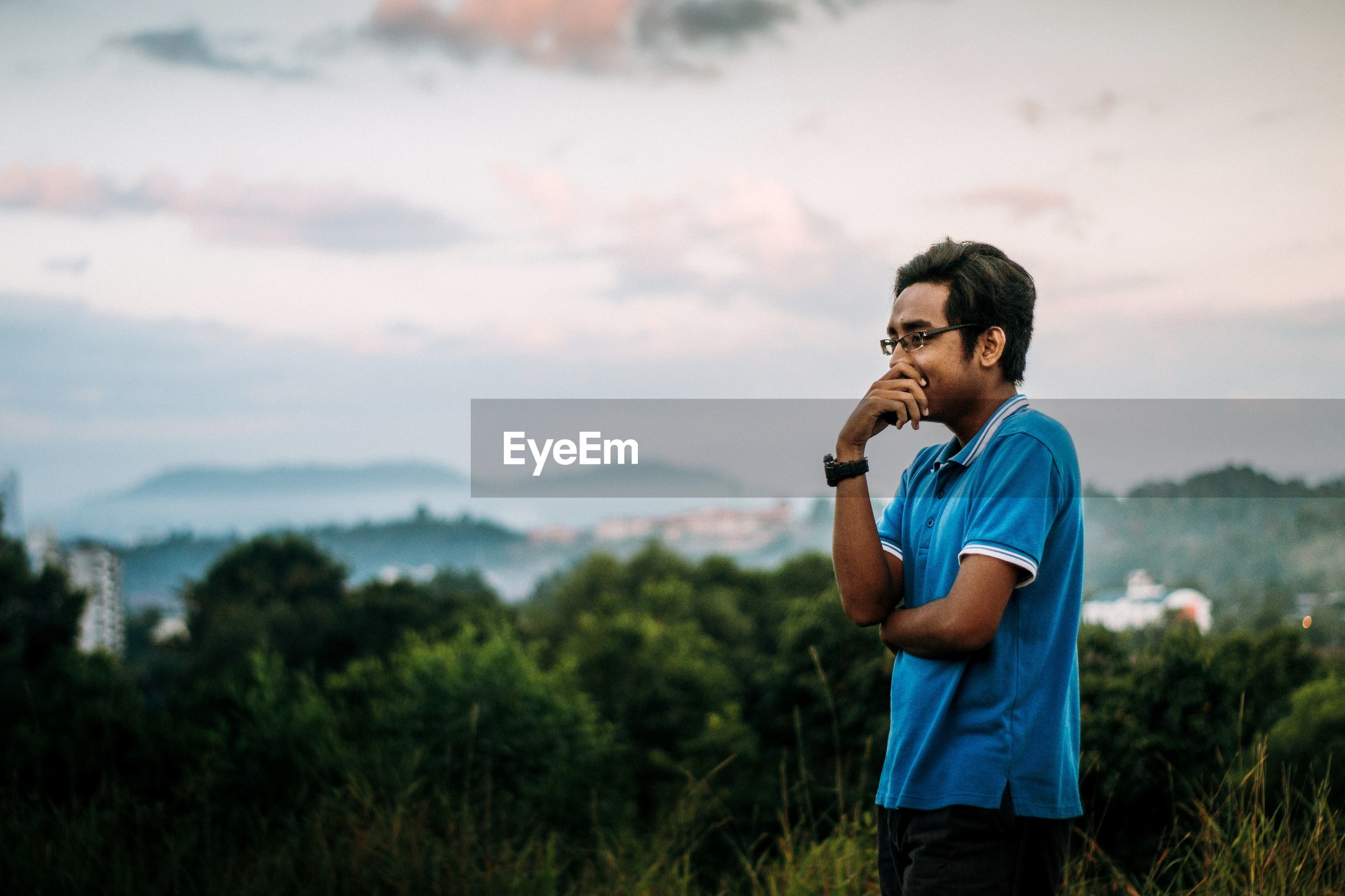 Young man looking away while standing in forest against sky