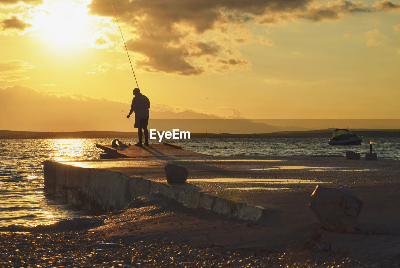 Rear view of man fishing in river at sunset