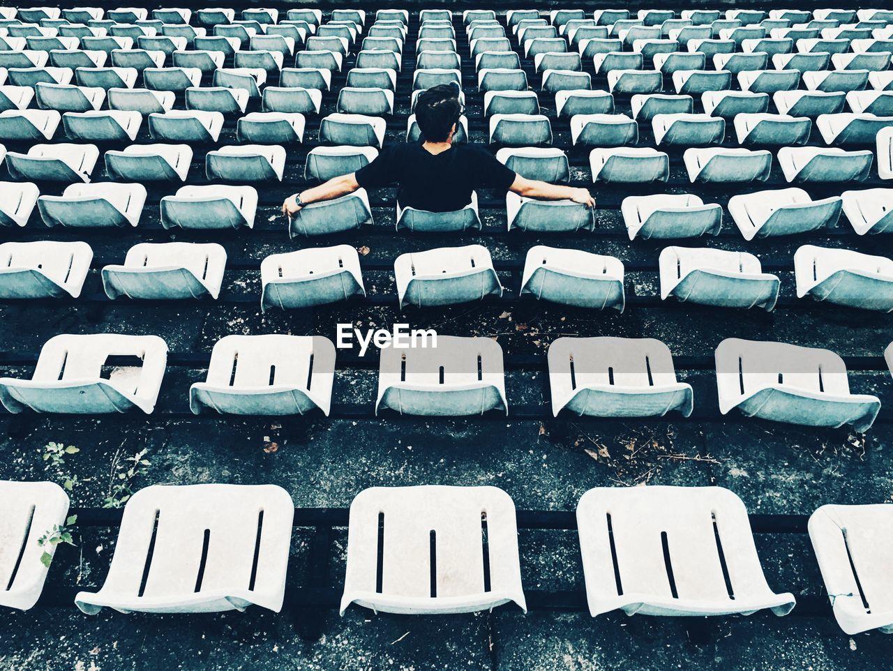 Full Length Of Man Sitting On Bleacher In Stadium