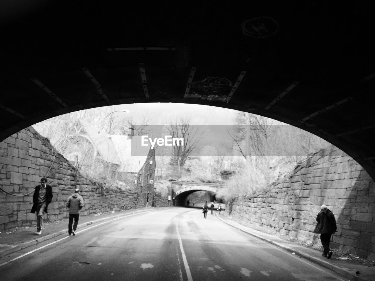 real people, walking, bridge - man made structure, transportation, connection, road, full length, arch, built structure, the way forward, men, lifestyles, architecture, medium group of people, tunnel, rear view, city life, day, leisure activity, travel destinations, women, outdoors, under, pedestrian, city, water, adult, people