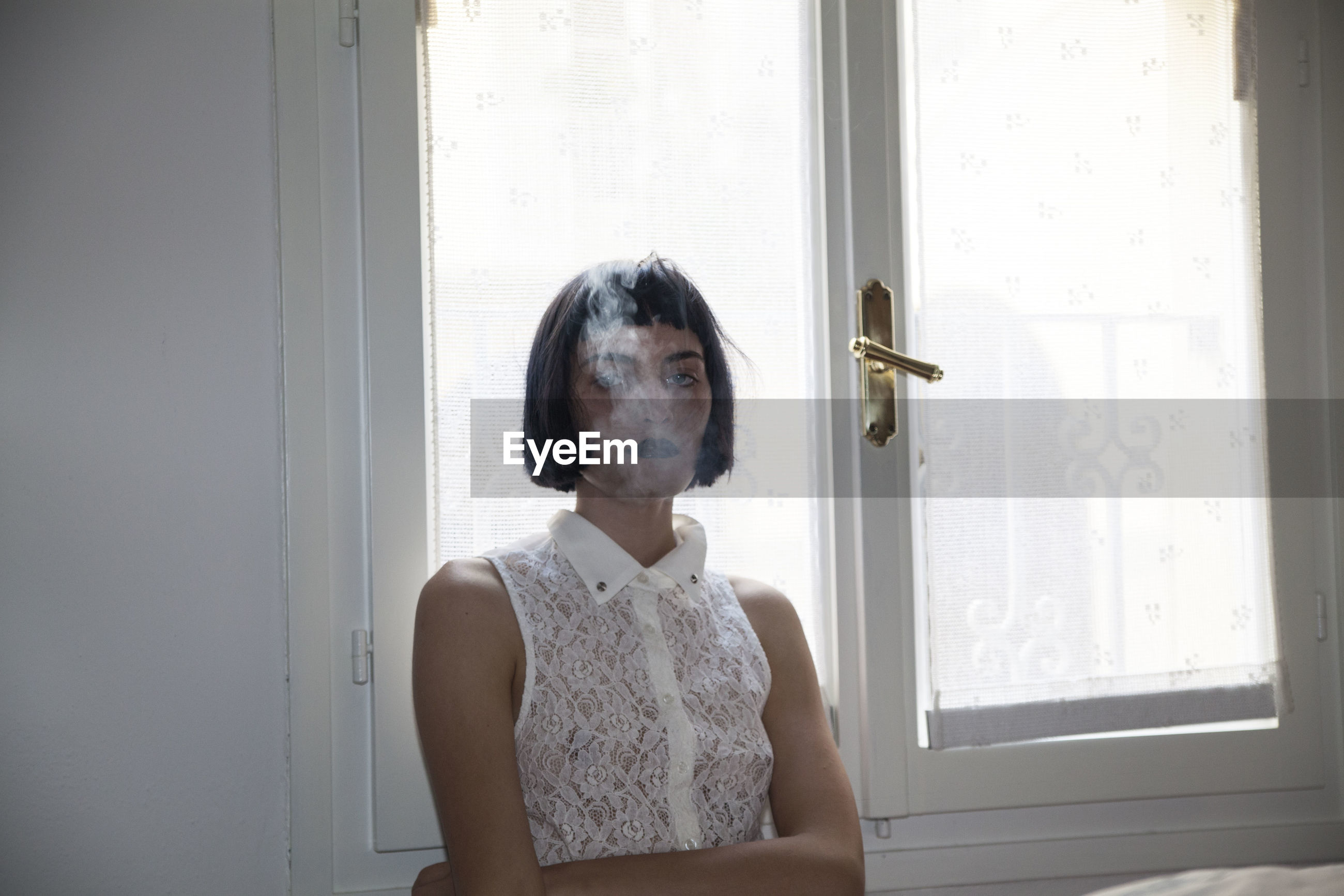 Portrait of woman smoking against window at home