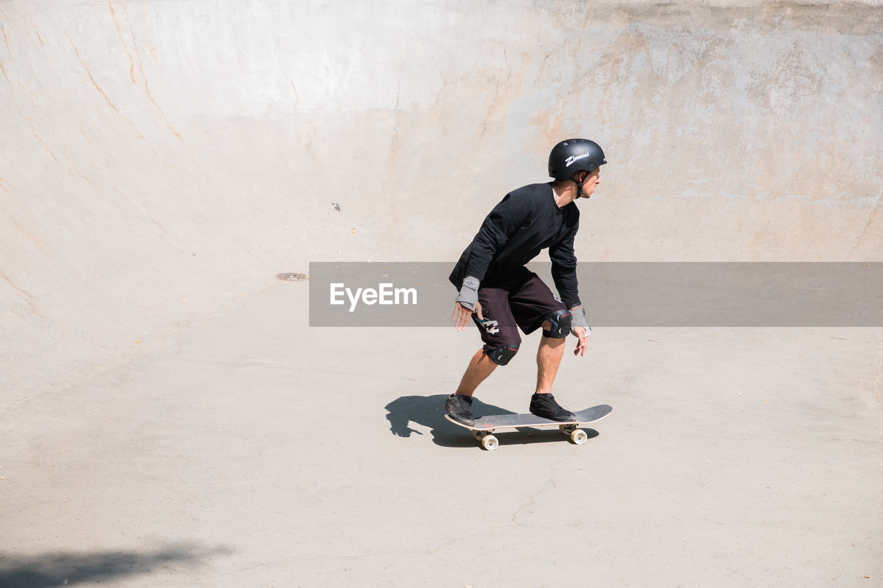 full length, lifestyles, one person, sports equipment, leisure activity, real people, casual clothing, men, helmet, sport, day, skill, skateboard, side view, young men, headwear, wall - building feature, shadow, balance, outdoors, concrete
