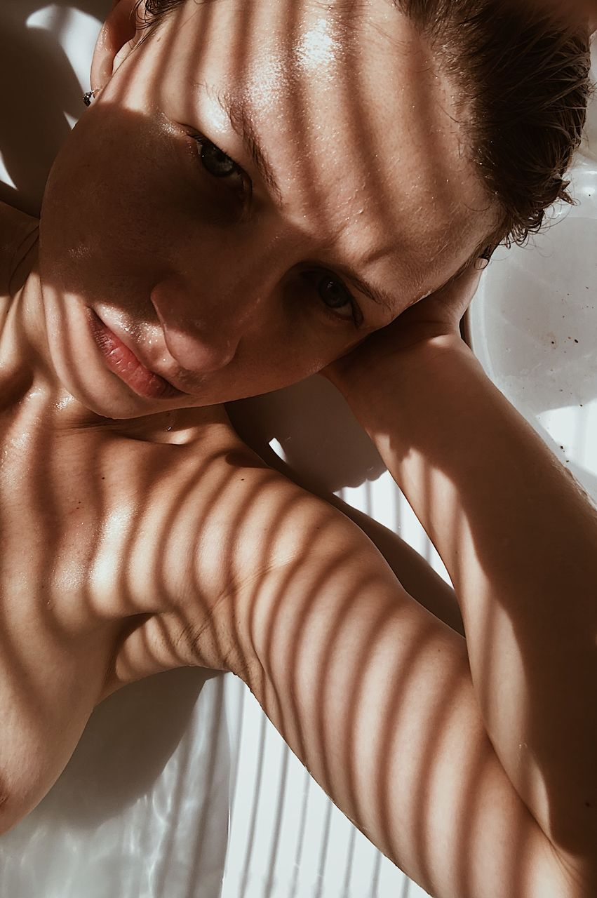 Close-up high angle portrait of shirtless woman at home
