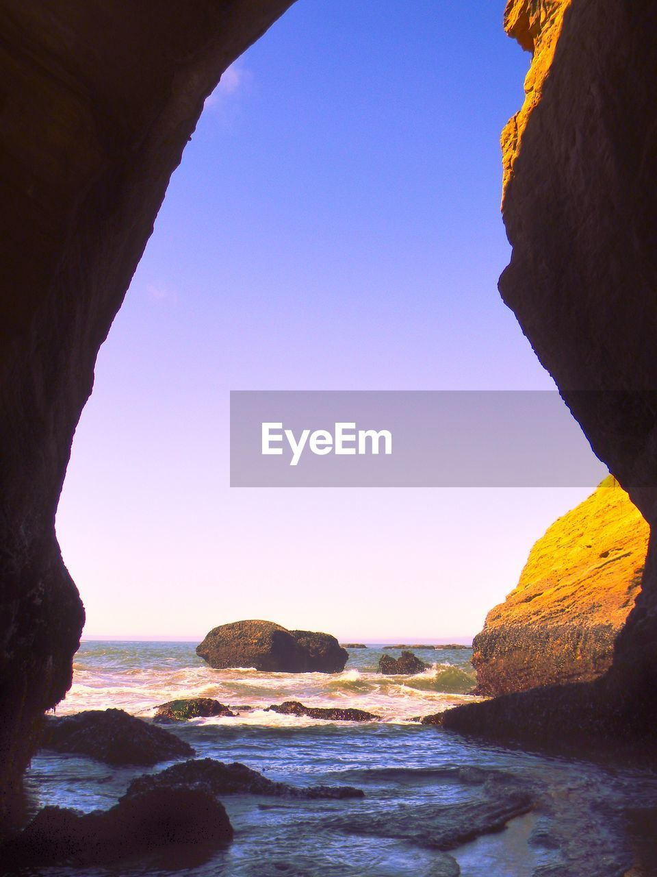 sea, rock formation, nature, rock - object, beauty in nature, scenics, tranquility, tranquil scene, clear sky, rock, no people, natural arch, horizon over water, outdoors, day, travel destinations, cliff, water, sky, beach, wave