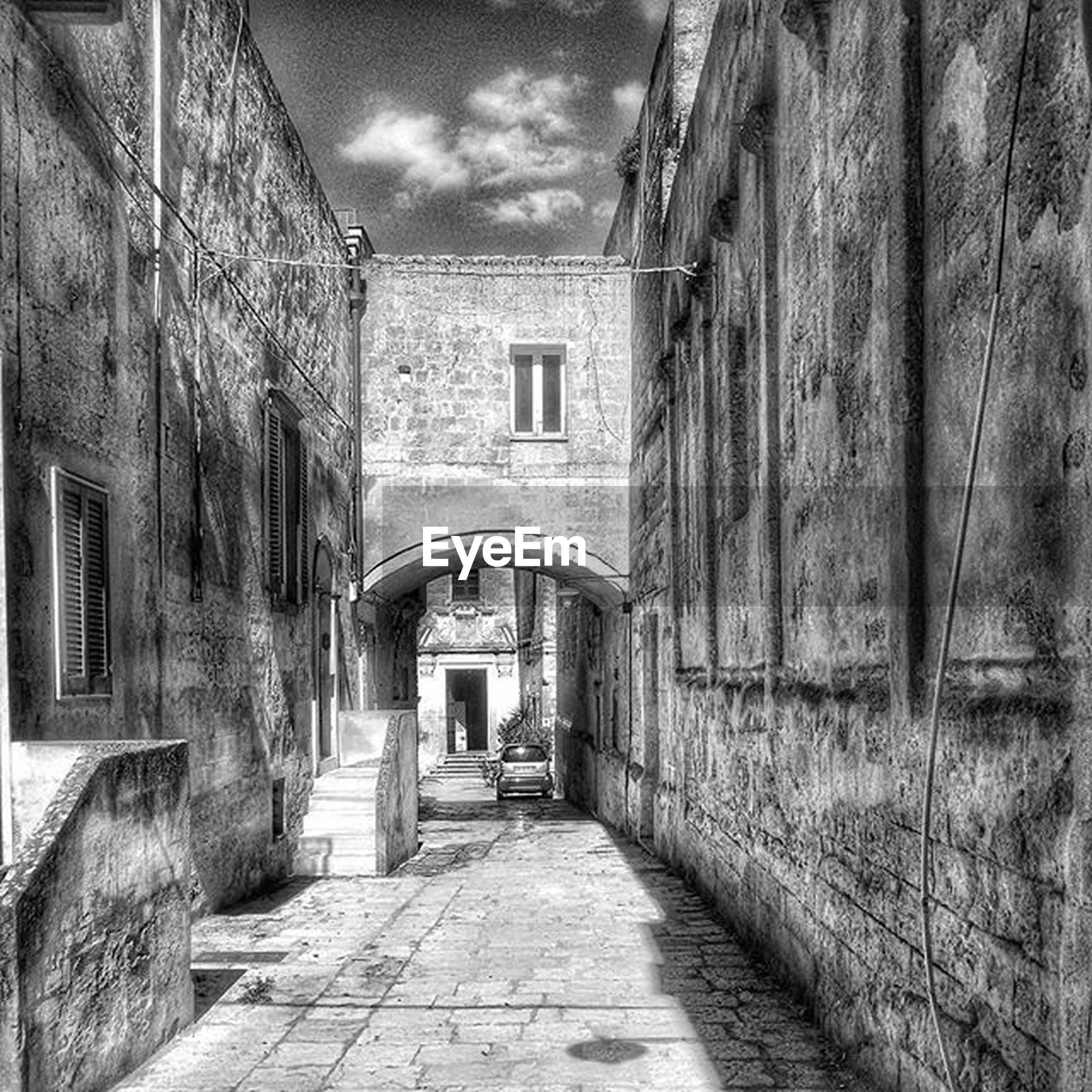 architecture, built structure, building exterior, the way forward, sky, narrow, house, walkway, diminishing perspective, door, building, pathway, arch, empty, residential structure, leading, cobblestone, day, cloud - sky, entrance