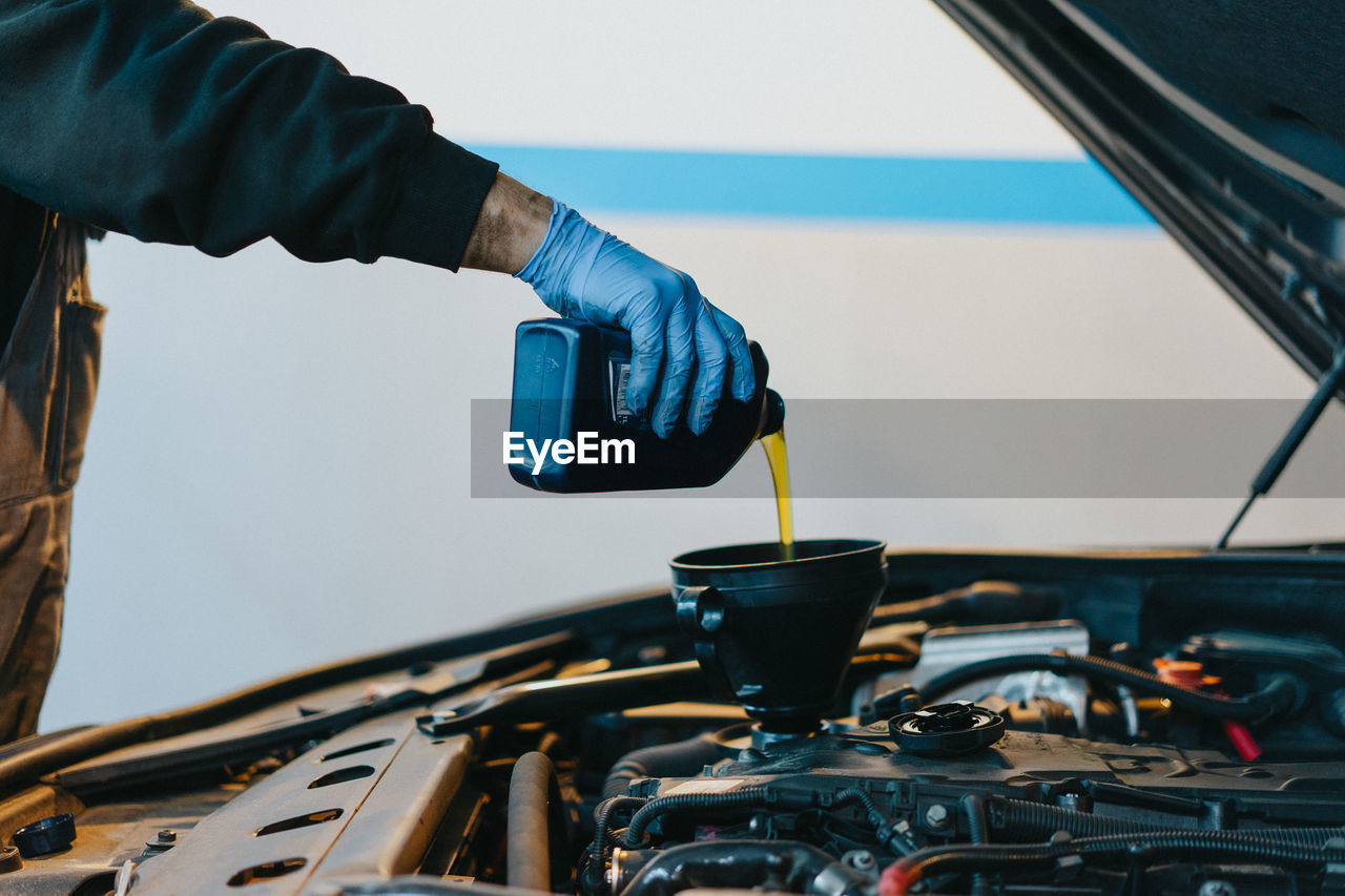 Cropped Hand Pouring Oil In Car Engine