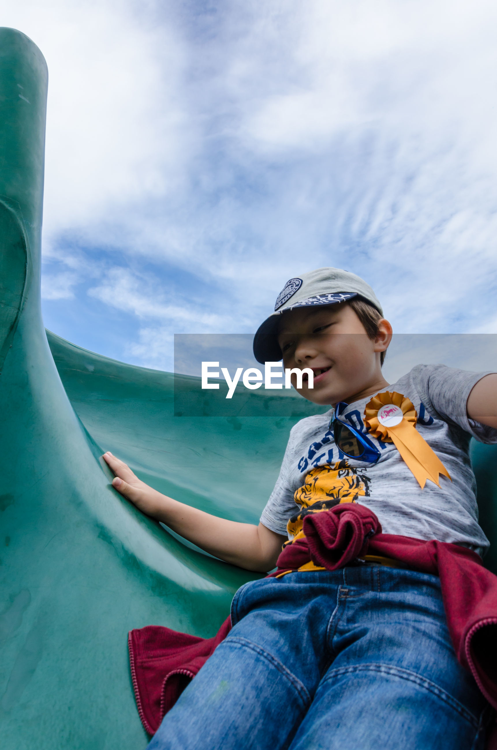 Low angle view of happy boy enjoying slide against sky