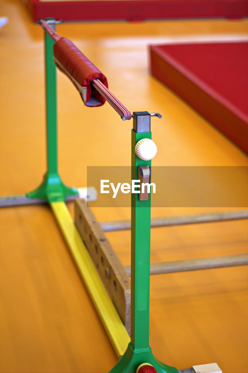no people, indoors, focus on foreground, metal, close-up, yellow, absence, day, empty, sport, multi colored, selective focus, in a row, wall - building feature, green color, table, equipment, steel, alloy
