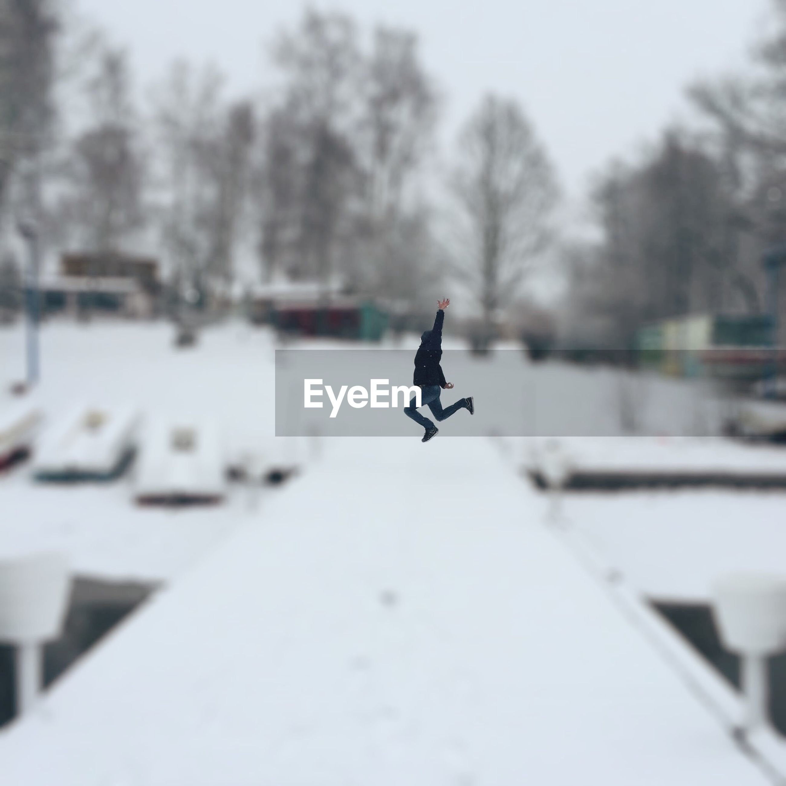 Tilt shift image of person jumping over snow covered walkway