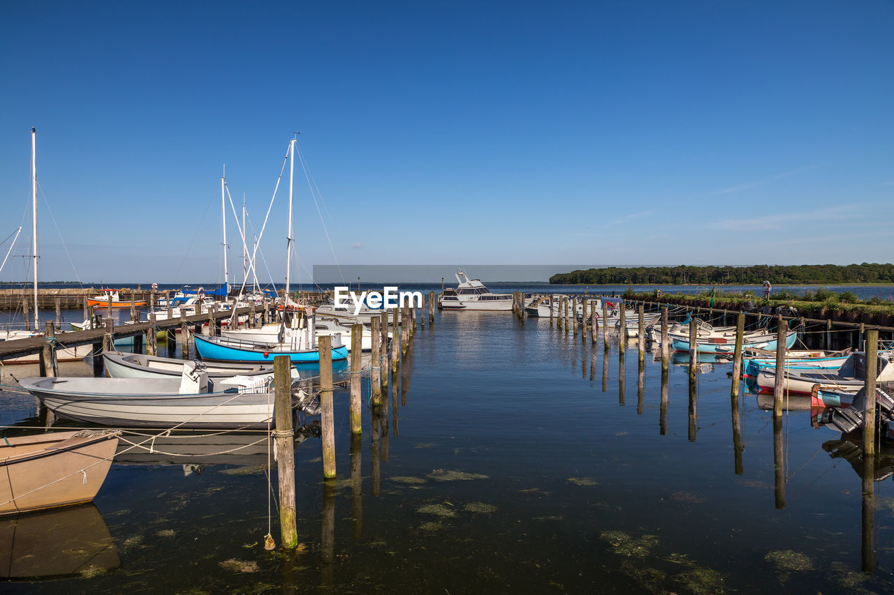 water, transportation, nautical vessel, sky, moored, mode of transportation, nature, sailboat, harbor, reflection, day, pole, no people, mast, copy space, clear sky, beauty in nature, tranquility, blue, outdoors, marina, wooden post, port, yacht