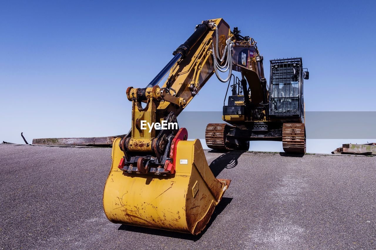Excavator on road against blue sky