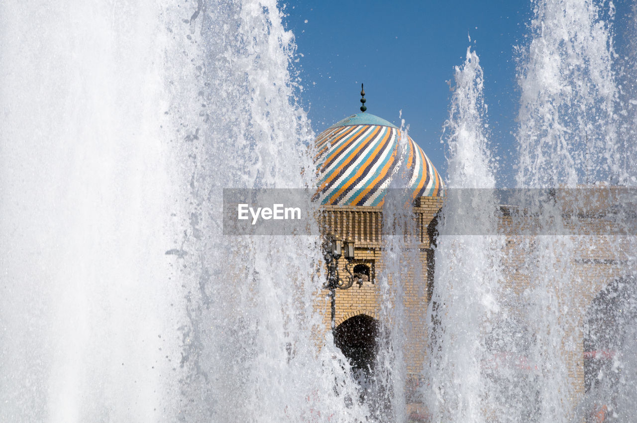 Water splashing in fountain against building