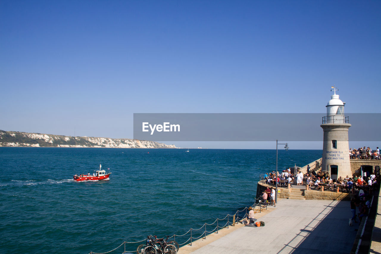 sea, water, sky, copy space, clear sky, built structure, group of people, architecture, blue, real people, nature, building exterior, nautical vessel, day, horizon, travel, large group of people, transportation, horizon over water, lighthouse, guidance, outdoors