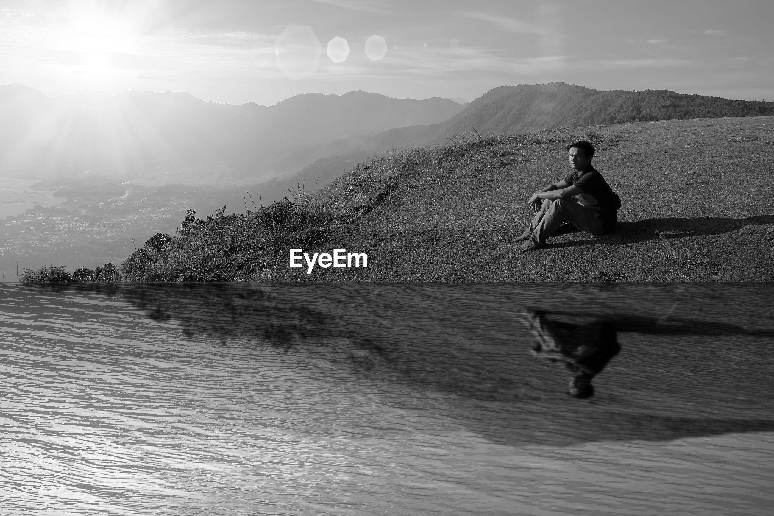 Reflection of man sitting at shore on lake