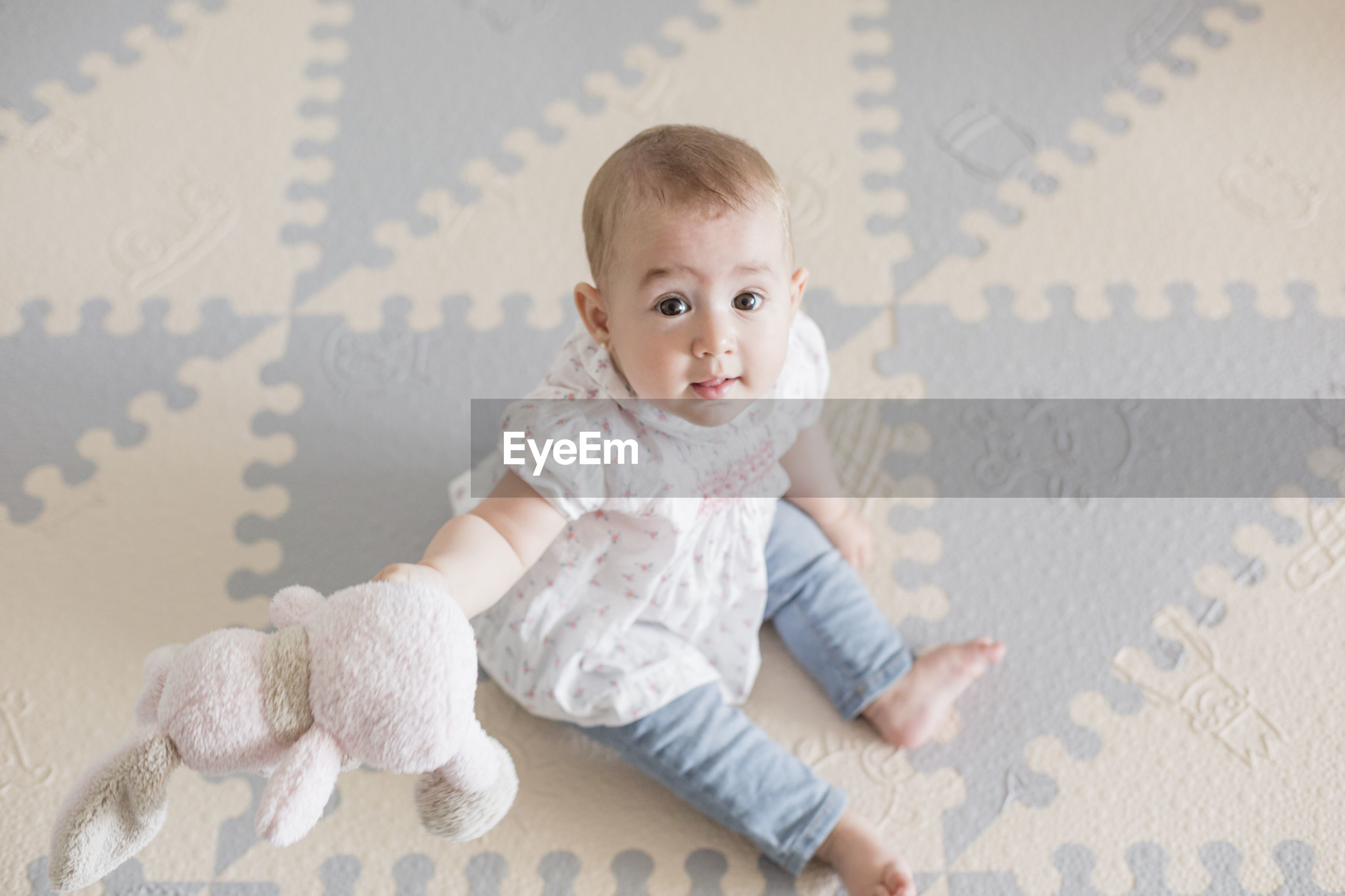 Cute baby girl playing with stuffed toy while sitting on mat