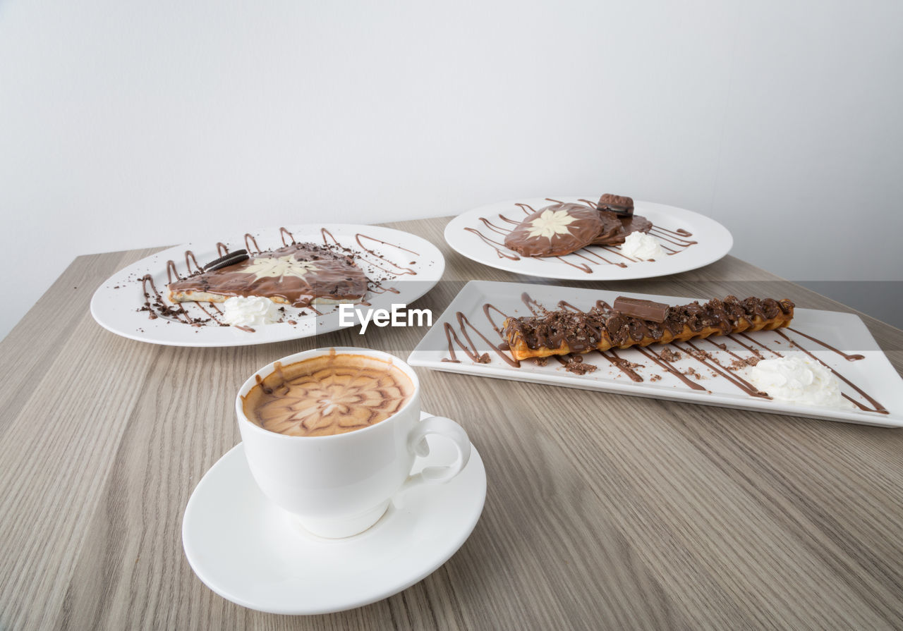 Close-up of coffee cup and desserts served on table