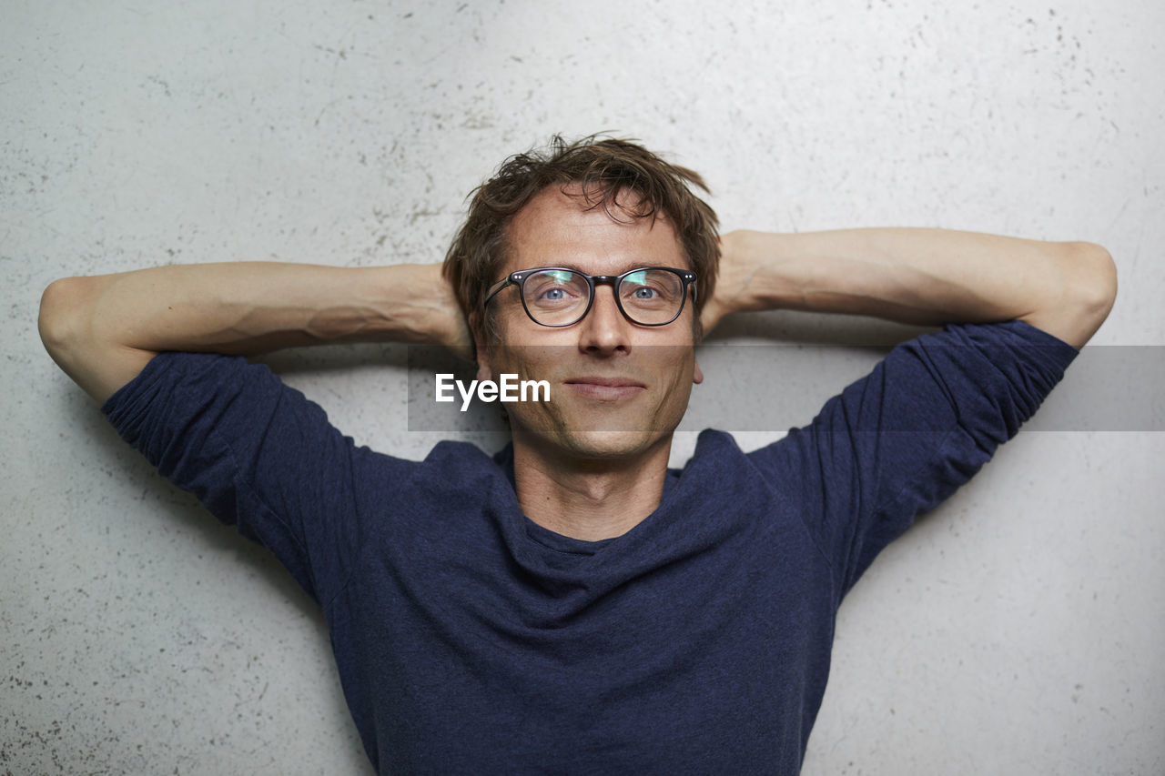 PORTRAIT OF YOUNG MAN WEARING EYEGLASSES AGAINST WALL AT HOME