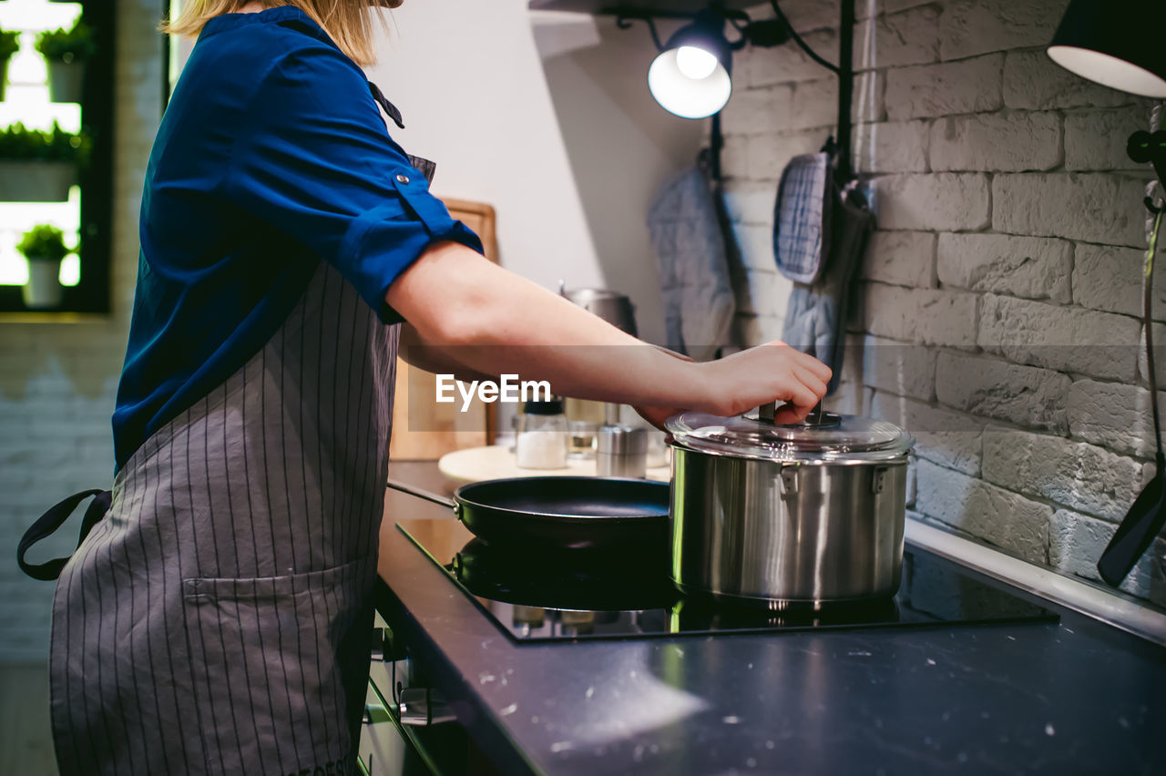 Side view of woman preparing food in kitchen