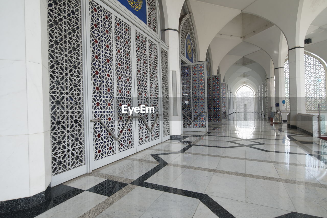 architecture, flooring, built structure, arch, indoors, tile, arcade, corridor, building, tiled floor, architectural column, pattern, no people, ceiling, empty, day, wall - building feature, the way forward, direction, colonnade, long
