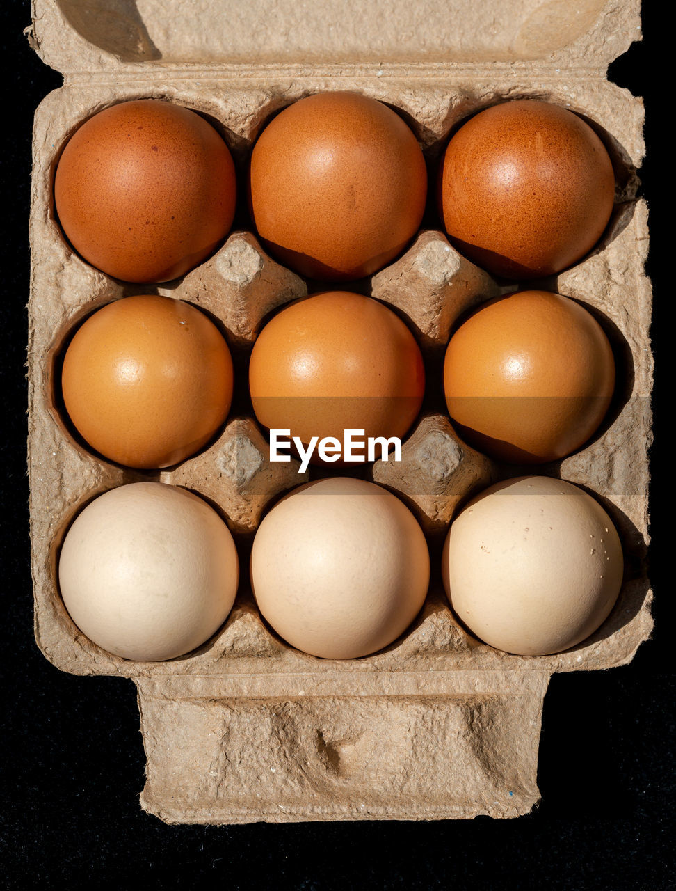 egg, food, food and drink, healthy eating, freshness, wellbeing, indoors, directly above, still life, egg carton, close-up, brown, no people, fragility, arrangement, vulnerability, raw food, in a row, side by side, container, order, black background, box - container, tray