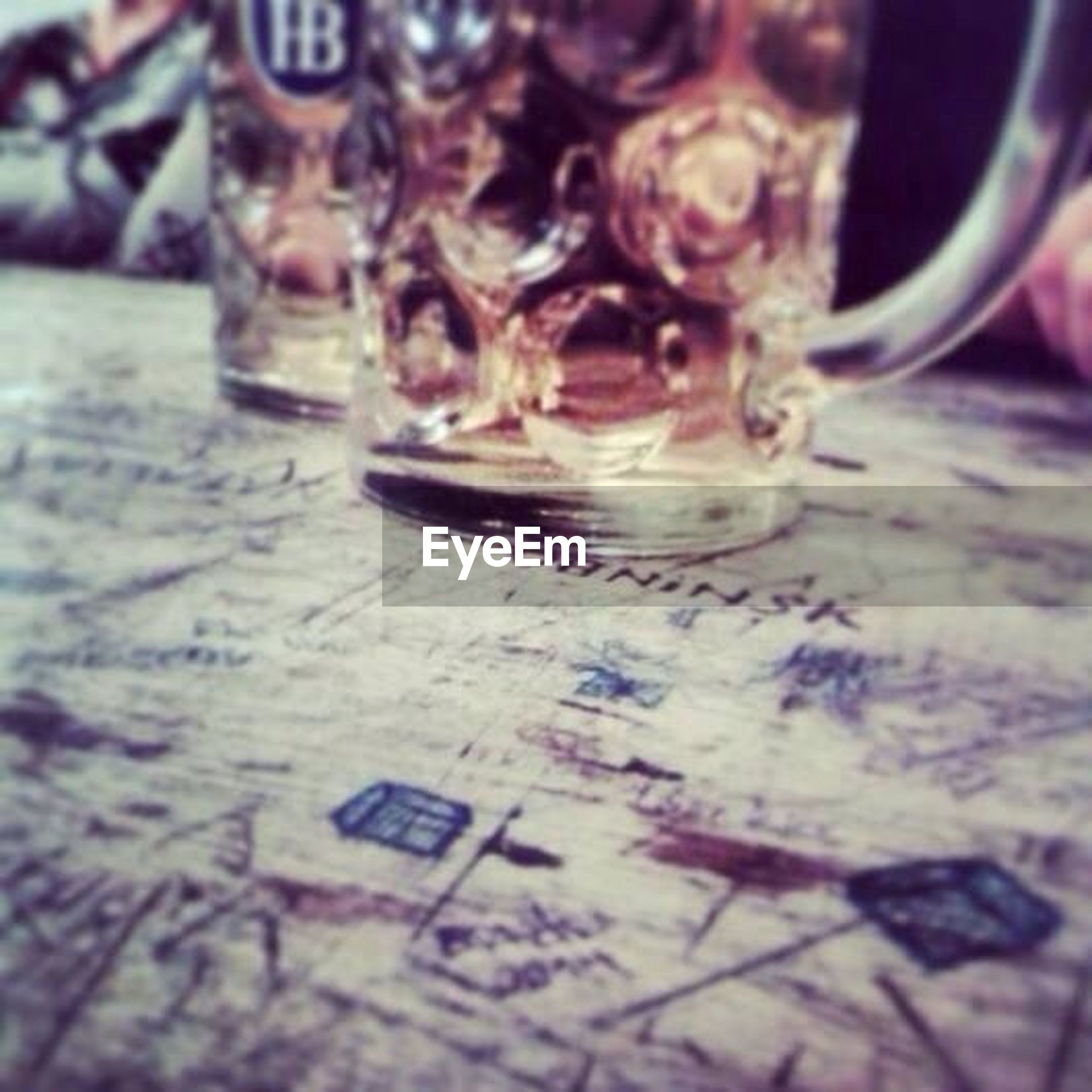 close-up, selective focus, focus on foreground, indoors, table, still life, text, no people, water, high angle view, day, reflection, glass - material, art and craft, western script, metal, bottle, human representation, drinking glass