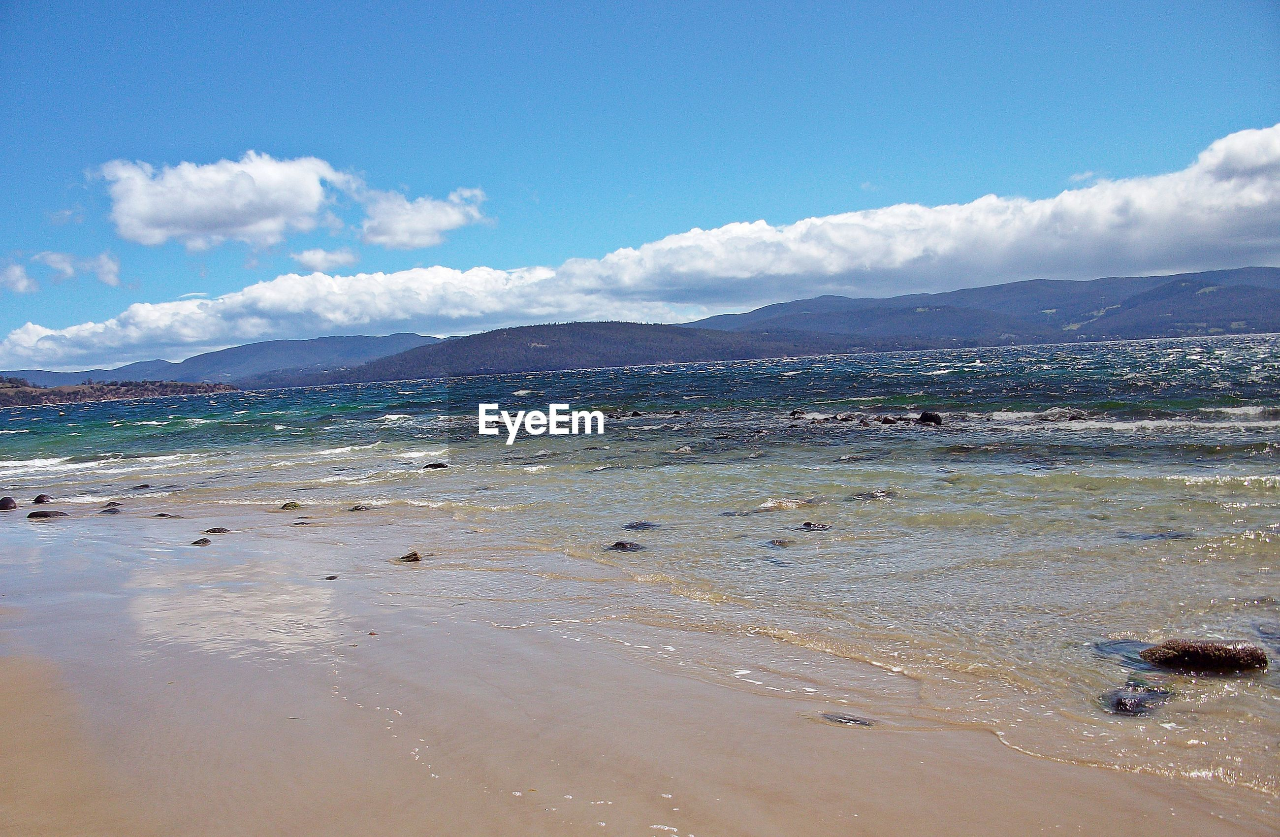 SCENIC VIEW OF BEACH AND MOUNTAINS AGAINST SKY