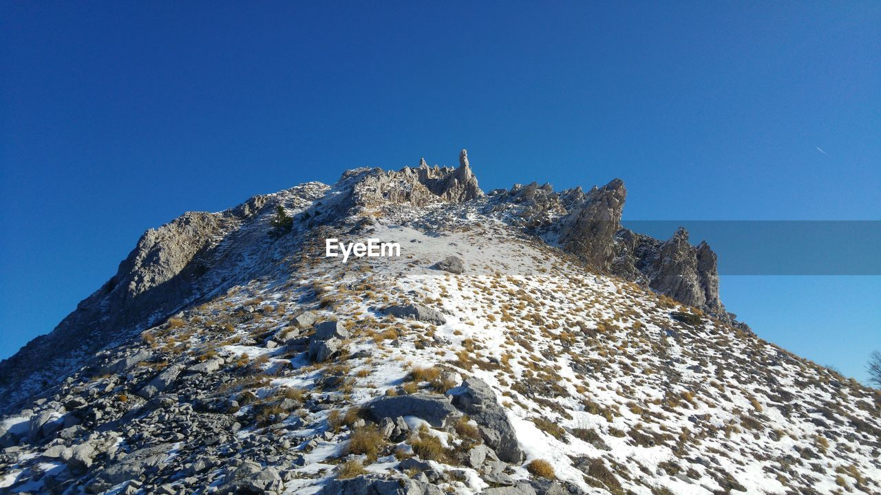 sky, low angle view, blue, clear sky, nature, day, rock, mountain, beauty in nature, solid, no people, copy space, rock - object, tranquility, outdoors, snow, scenics - nature, sunlight, winter, mountain peak, formation, snowcapped mountain