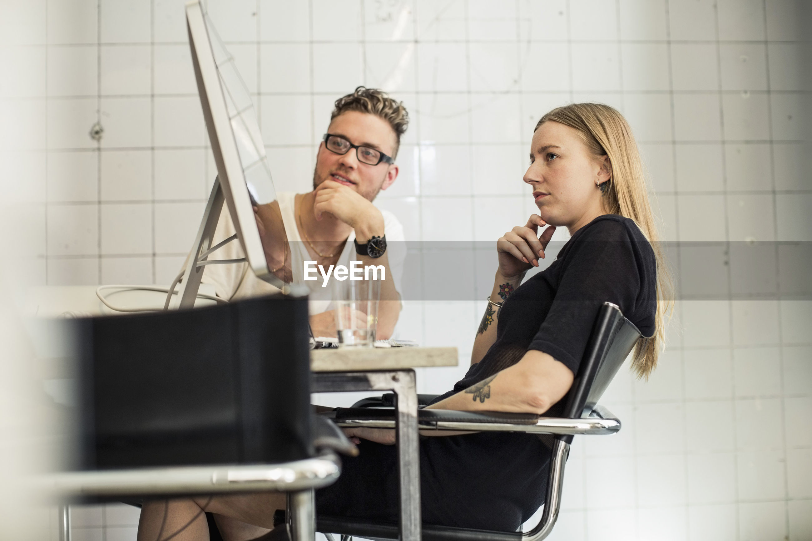YOUNG WOMAN USING MOBILE PHONE IN OFFICE