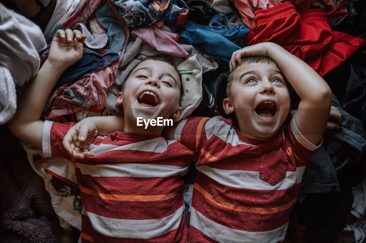 High angle view of laughing boys lying on clothes at home