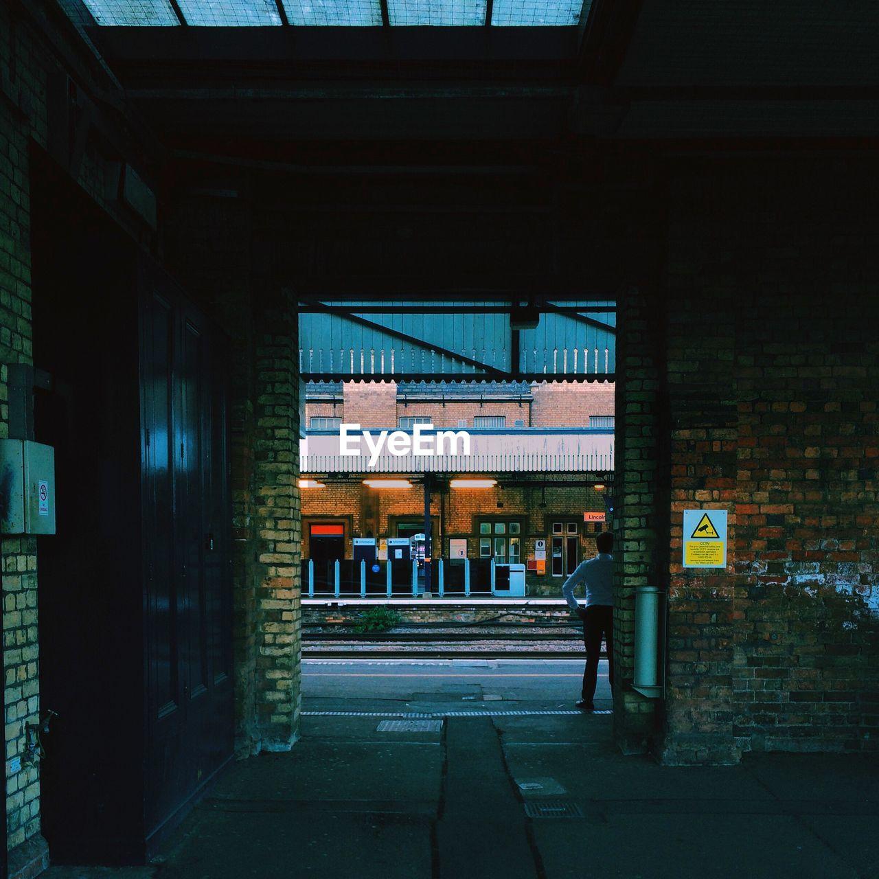 Rear view of man waiting at railroad station
