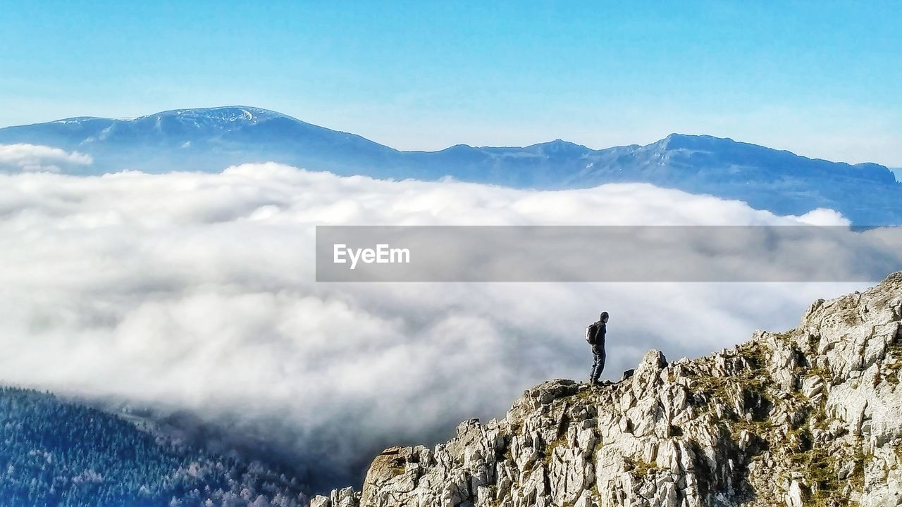 mountain, beauty in nature, scenics - nature, leisure activity, sky, mountain range, one person, nature, cloud - sky, adventure, tranquil scene, tranquility, real people, activity, day, standing, rock, men, lifestyles, non-urban scene, outdoors, mountain peak, formation