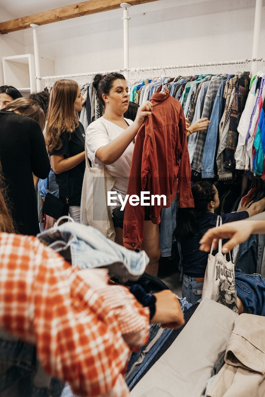 clothing, shopping, choice, retail, casual clothing, women, real people, store, adult, fashion, clothing store, clothes rack, rack, indoors, people, variation, business, coathanger, lifestyles, standing, consumerism, sale