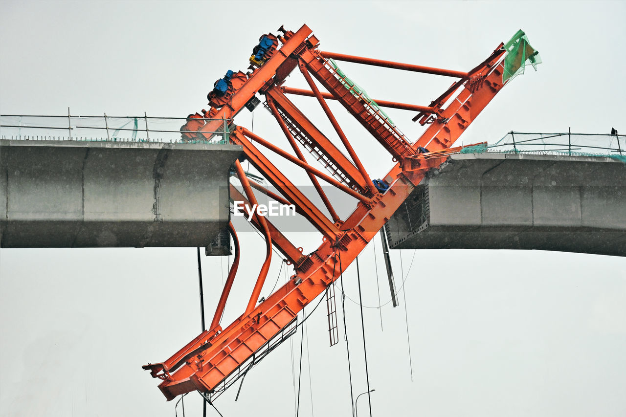 sky, industry, metal, machinery, construction industry, nature, architecture, built structure, construction site, crane - construction machinery, clear sky, no people, low angle view, transportation, development, orange color, day, outdoors, connection, bridge, industrial equipment, construction equipment, girder