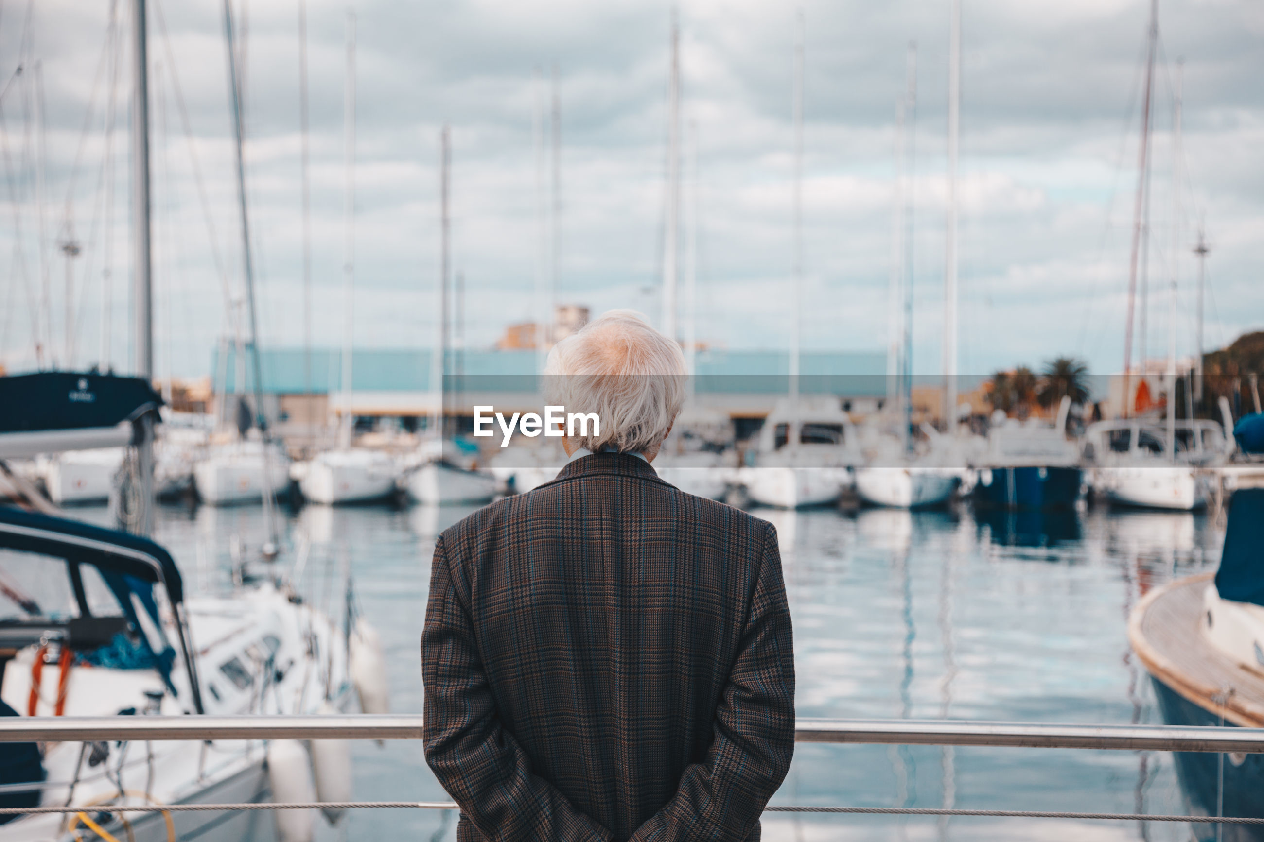 Rear view of senior man with hands behind back standing by railing at harbor