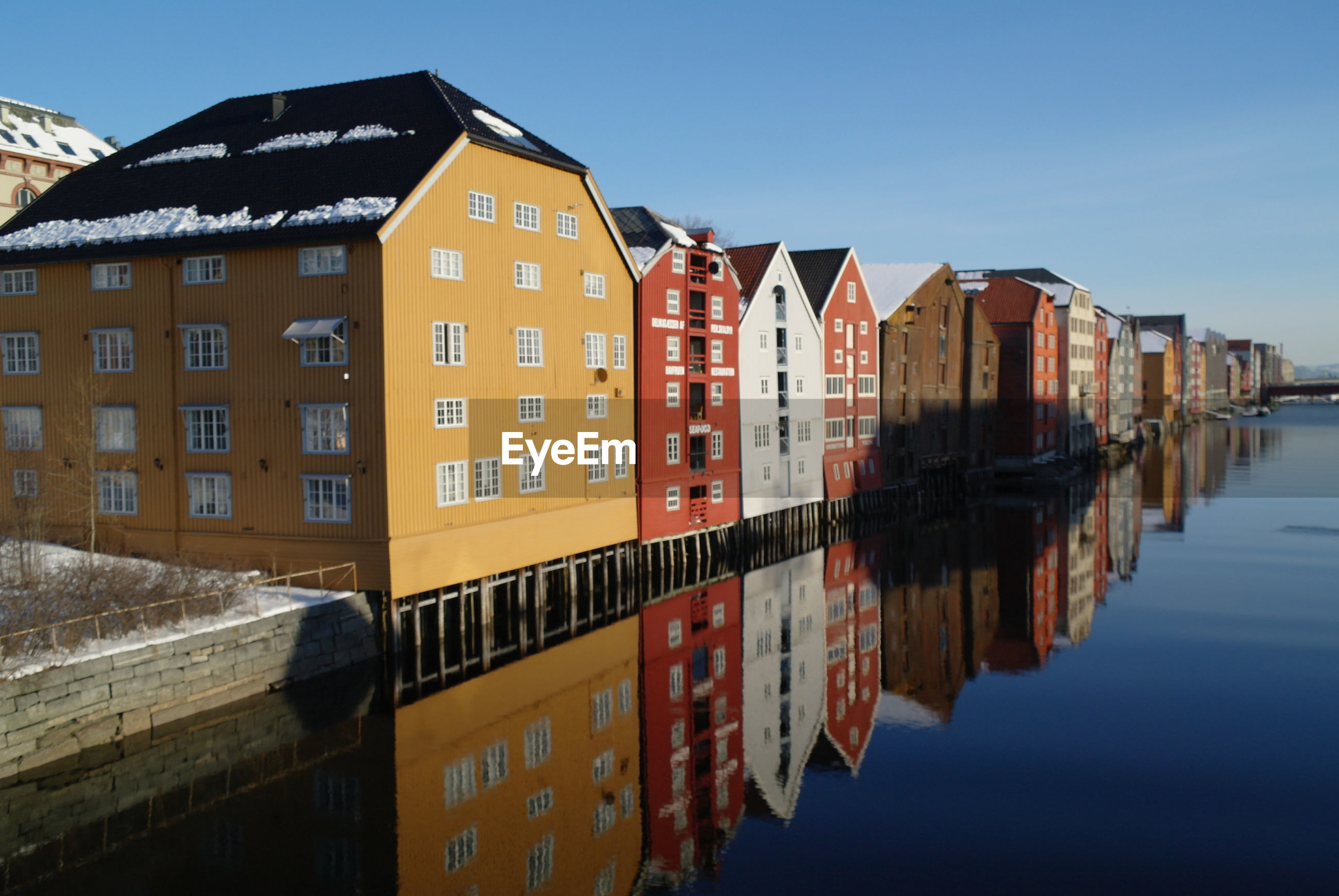 Reflection of buildings in canal against clear sky
