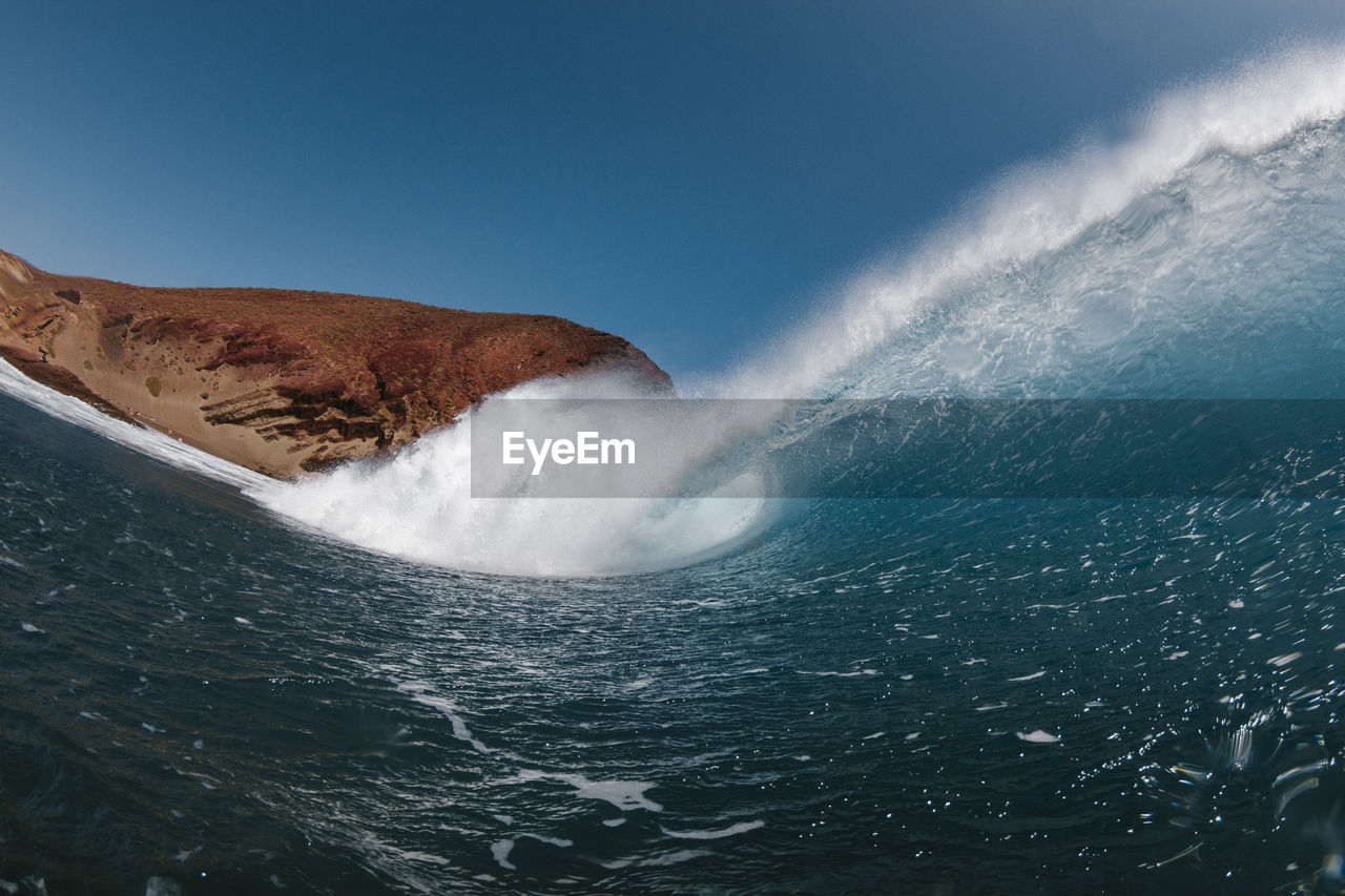 Scenic view of sea waves splashing against blue sky